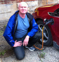 Photo of Mark next to his plugged in Volt EV